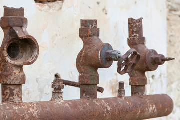 Old corroded water pipe with broken faucets
