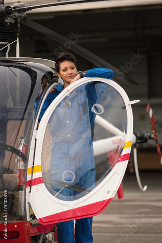 Young woman helicopter pilot. - 73403396