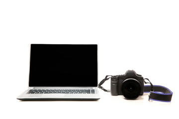 Laptop with blank screen and photo camera side by side