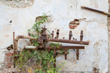 Old corroded water pipes with broken faucets