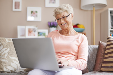 Senior woman relaxing with laptop on sofa