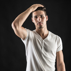 Portrait of confident young man wearing white shirt against blac