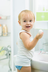 child toddler washing hands with soap in bathroom