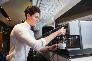 Smiling young barista making cup of coffee