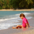 Small girl sitting on sand