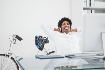 Relaxed designer with headphones leaning back in his chair