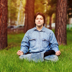 Young man meditating outdoors