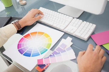 Designer using computer and colour wheel