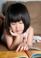 Asian little girl reading her book