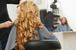 Blonde curly hair. Hairdresser doing hairstyle for young woman i - 73406787