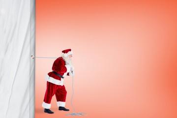 Santa claus pulling rope against orange