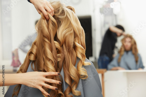 canvas print picture Blonde curly hair. Hairdresser doing hairstyle for young woman i