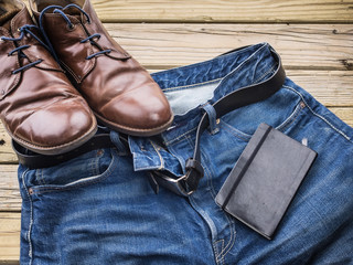 detail of blue jeans with black leather belt  shoes and notebook