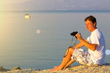 Man with binoculars at the beach