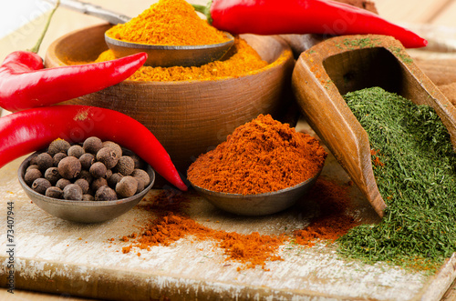 spices on spoons on  wooden background - 73407944