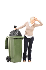 Disgusted woman standing next to a trash can