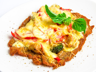 Crispy veal schnitzel with cheese, tomatoes, peppers, broccoli