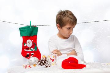 Portrait of sad boys with Christmas decorations.