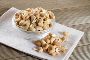 Bowl with cashew on a wooden background