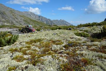 Backpack lies on the high meadows Barguzinsky Ridge on Lake Baik