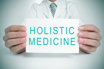 doctor with a signboard with the text holistic medicine