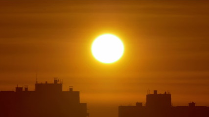 The sunrise above city buildings, close-up view