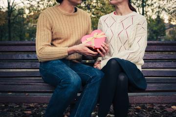 Man giving woman heart shaped box