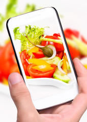 Hands taking photo salad  with smartphone