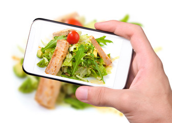 Hands taking photo grilled salmon and vegetables with smartphone