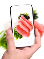 Hands taking photo pieces of tuna and salad  with smartphone