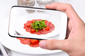 Hands taking photo meat with smartphone
