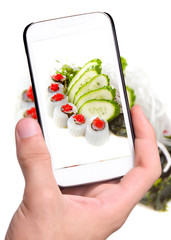 Hands taking Scallops with salad with smartphone