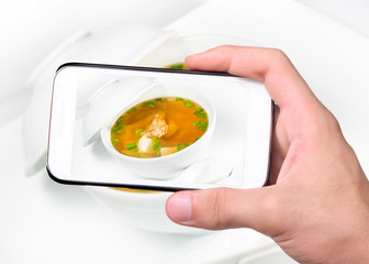 Hands taking photo soup with  shrimp  with smartphone