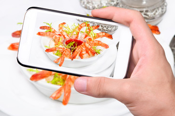 Hands taking photo shrimps with smartphone