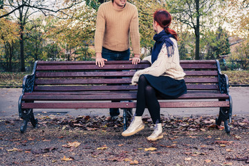 Young man and woman talking in park