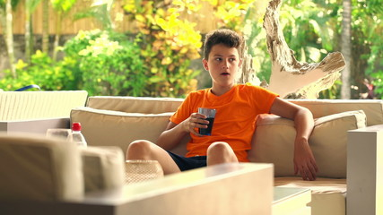 Young boy drinking soda and relaxing on sofa at home