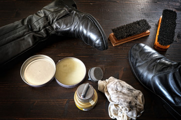 Shoes and polishing equipment on dark brown wooden surface