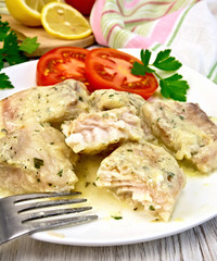 Fish stew in creamy sauce with tomatoes in plate on board