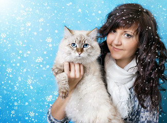 Young woman with siberian cat in snow