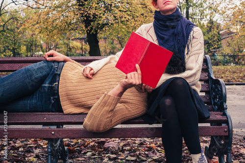 Couple reading and relaxing in park