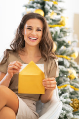 Portrait of young woman opening envelope near christmas tree