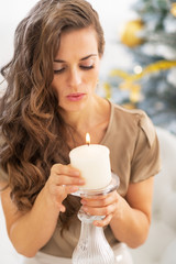 Portrait of young woman blowing candle