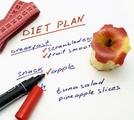 Diet plan with apple, marker and measuring tape