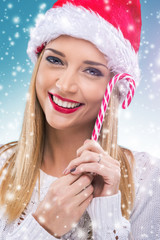 Woman with santa hat holding red -white Christmas Lollipop