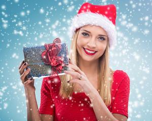 Beautiful woman with santa hat, holding gift box - snowfall