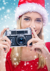 Beautiful woman with santa hat, holding the camera - snowfall