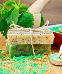 Soap homemade and candle with nettles in mortar on board