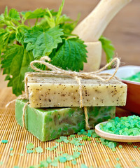 Soap homemade with nettles in mortar on board