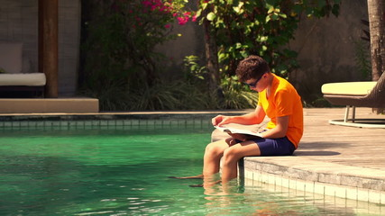 Teenager sitting with book on the edge of swimming pool
