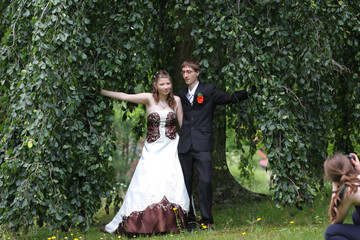 Bride and groom in summer park with photographer